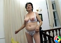 Mature hottie with curvy body and perky tits playing with banana
