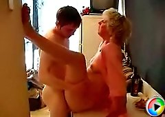 The mature house-wife was drunk in the kitchen when her son's best friend embraced her from behind and gently rubbed her slit